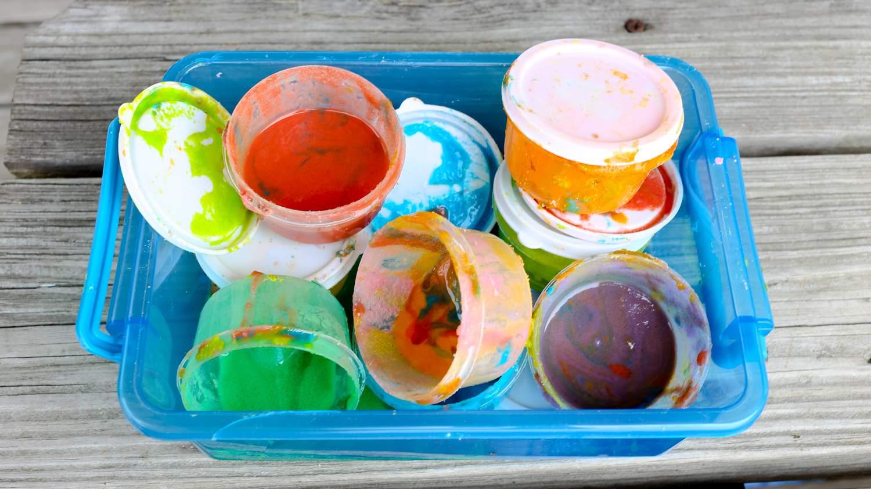 Pintura casera guardada en pequeños recipientes plásticos