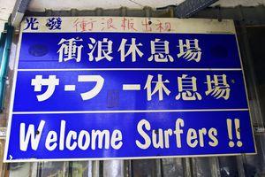 tienda de surf con cartel de bienvenida en chino, japonés y inglés.