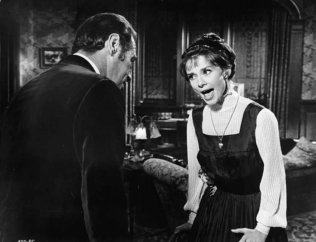 Rex Harrison escucha a Audrey Hepburn cantando 'The Rain in Spain' en una escena de la película 'My Fair Lady'