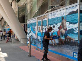 Un artista pintando un mural de mar y barco