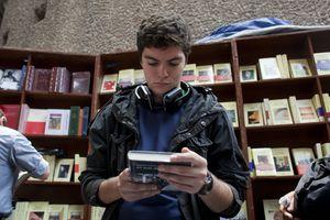 Un joven mirando la portada de un libro