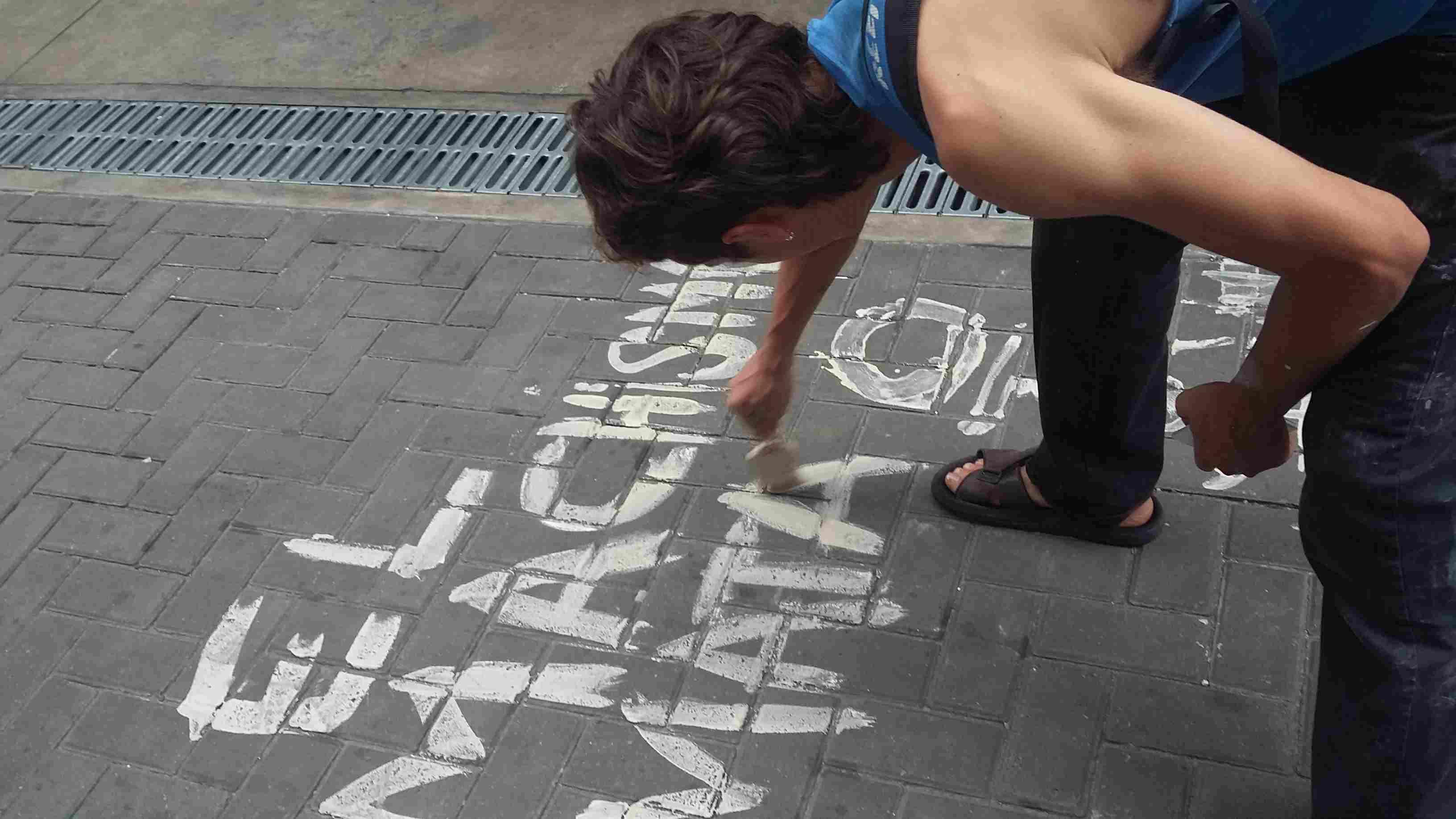 Muchacho escribiendo un grafitti contra el machismo.
