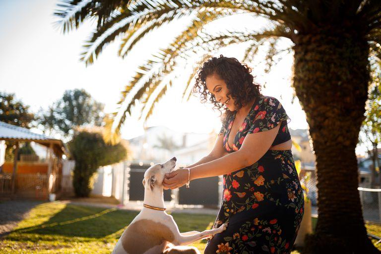 Mujer embarazada jugando con su perro