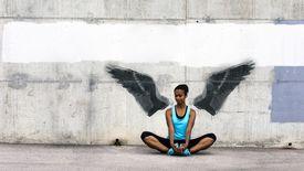 Mujer joven sentada y estirada frente a un muro de hormigón con alas de ángel pintadas