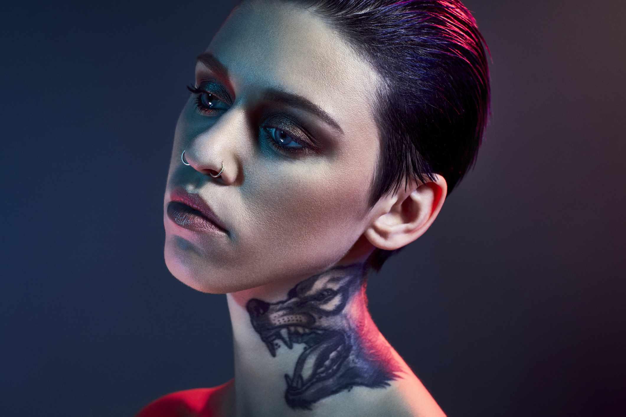 Una mujer joven con un tatuaje de lobo en el cuello posa para un retrato
