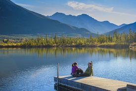 Couple on dock, Vermilion Lake, Banff National Park, Alberta, Canada