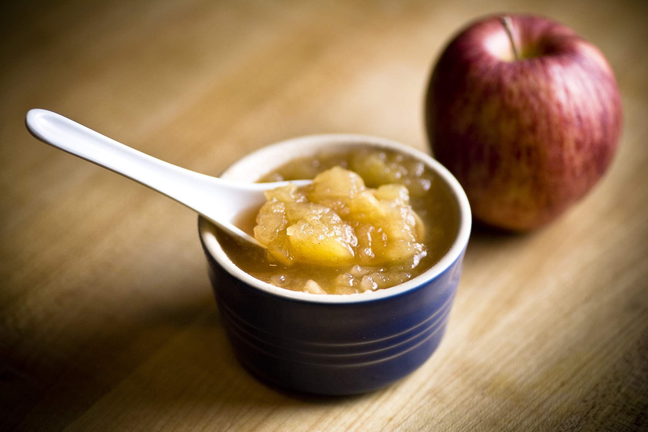 Home-made apple sauce in a blue dish next to a red apple on a wooden table.