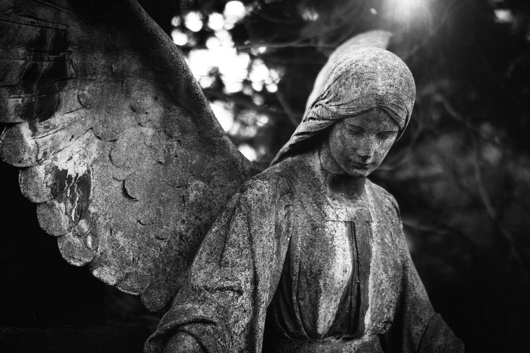 Low Angle View Of Angel Statue In Cemetery