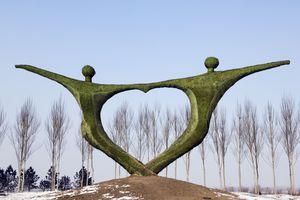 estatua de dos personas tomados de la mano en forma de corazón