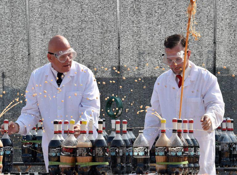 Botellas de coca-cola están explotando a medida que los hombres en batas de laboratorio dejan caer Mentos dentro