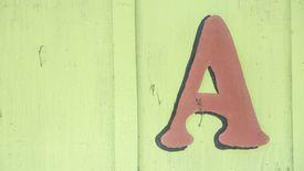 Mayúscula A pintada en una pared de madera