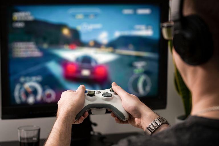 Un hombre está jugando un juego de carreras en su computadora