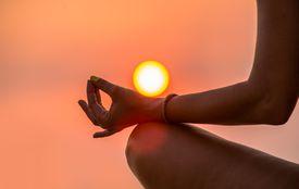 Una mujer medita en la posición de loto bajo un cielo naranja al amanecer