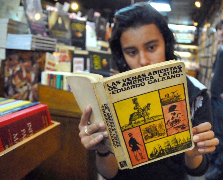 """Una joven echa un vistazo a una edición usada de 1971 de """"Las venas abiertas de América Latina"""" de Eduardo Galeano, en una biblioteca de segunda mano en Montevideo."""