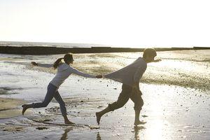 Mujer persiguiendo hombre en la playa