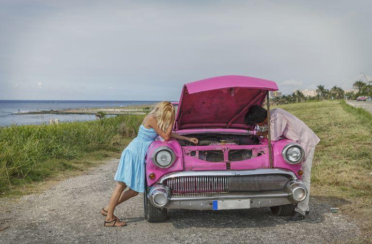 Pareja joven tratando de arreglar un convertible vintage en la costa
