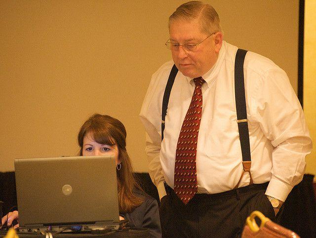 Hombre de mediana edad junto a mujer con ordenador portátil