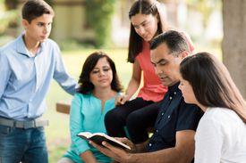 Una familia sentada afuera y leyendo la Biblia juntos
