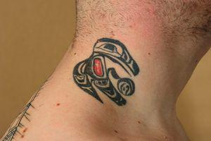 Tatuaje tribal de pájaro en el cuello con muchos lunares