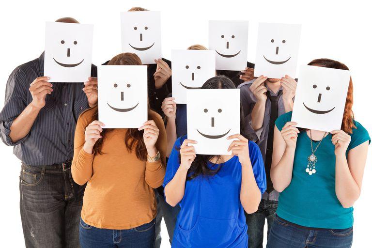 Grupo de personas todos con papeles con emoticones impresos en ellos