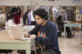 Estudiante con una computadora portátil en una biblioteca