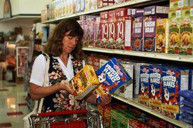 Mujer comparando cereales para el desayuno en el supermercado