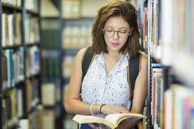 Niña leyendo un libro en la biblioteca