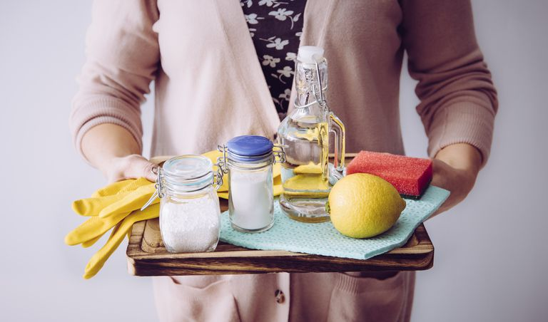 Natural cleaners concept. Woman holding eco friendly home cleaning ingredients, white vinegar, lemon, baking soda, citric acid concept.