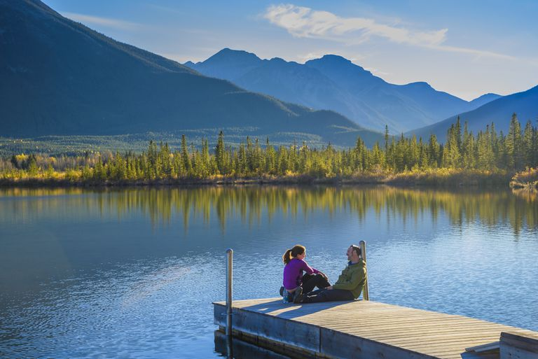 Couple on dock, Vermilion Lake, Banff National Park, Alberta, Canada